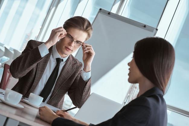 Бизнесмены в офисе, работая вместе, сидя человек, глядя на