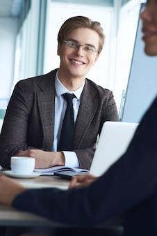 Бизнесмены в офисе, работая вместе, сидя человек, глядя ca