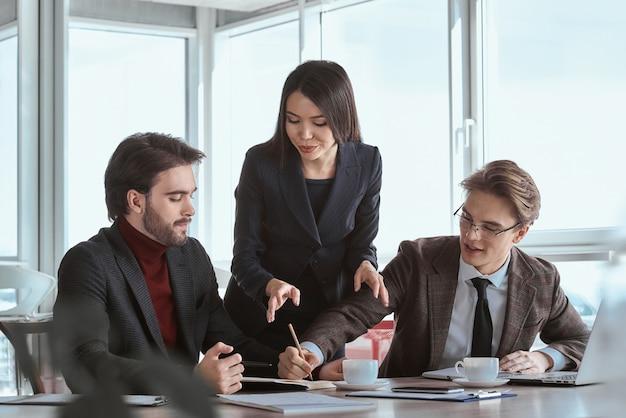 Бизнесмены в офисе, работая вместе, сидя, подписывая контра