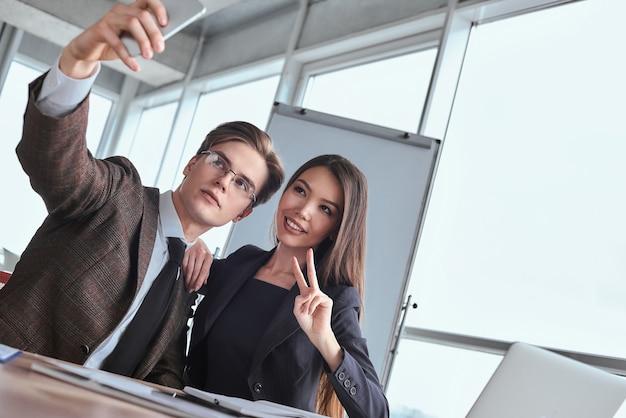 Бизнесмены в офисе, работая вместе, сидя, принимая селфи
