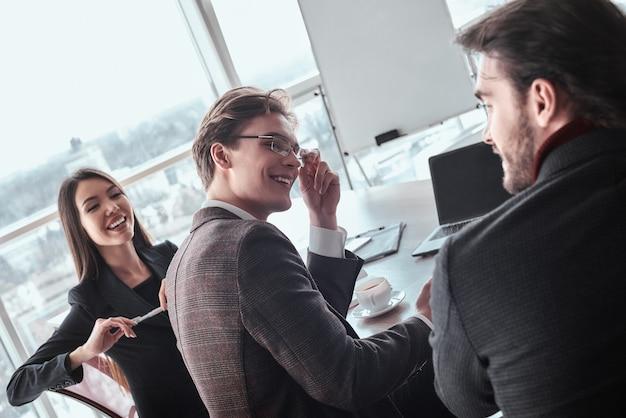 Бизнесмены в офисе, работая вместе сидя говорят шеф-повар