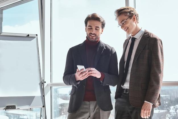 Бизнесмены в офисе, работая вместе, стоя, просматривая inte