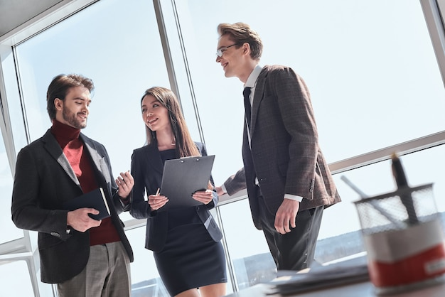 Бизнесмены в офисе, работая вместе стоя обсуждают pr