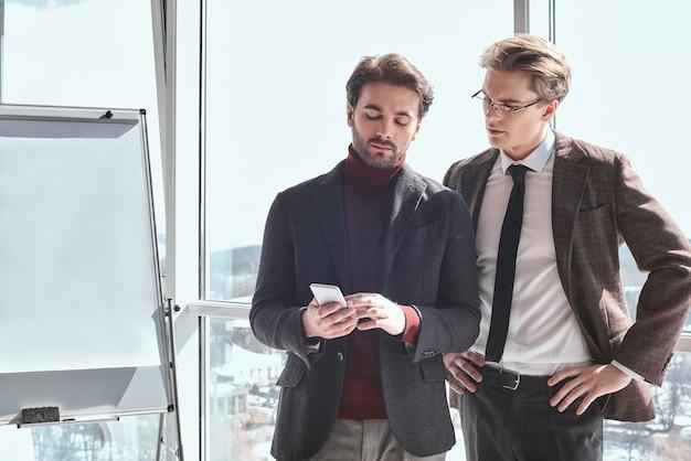Бизнесмены в офисе, работая вместе, стоя, глядя на бу