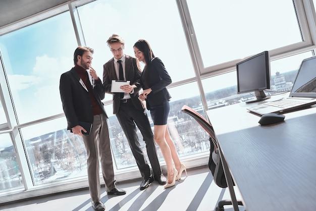 Бизнесмены в офисе, работая вместе, постоянный просмотр человека.