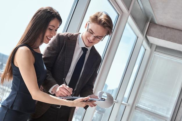 Бизнесмены в офисе, работая вместе, стоя человек, подписывающий