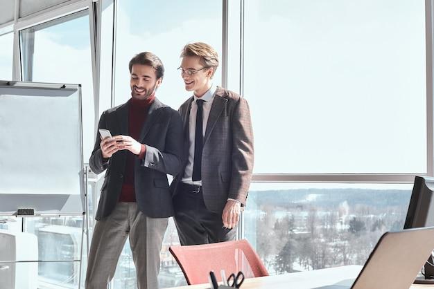 Бизнесмены в офисе, работая вместе, стоя с помощью smartph