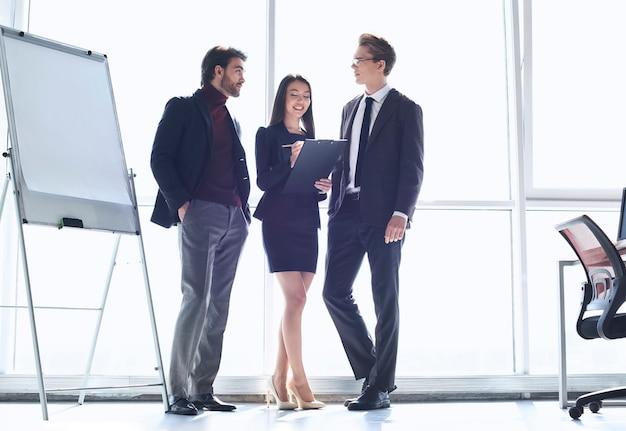 Бизнесмены в офисе, работая вместе стоя женщина принимая
