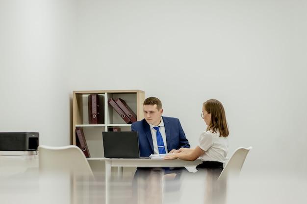 Деловые люди в коворкинге сравнивают информацию о настольном компьютере с бумажным документом в офисе