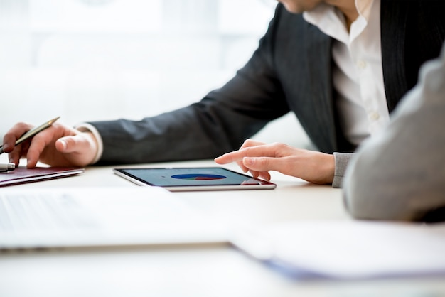 Бизнесмены обсуждают бизнес с помощью планшета