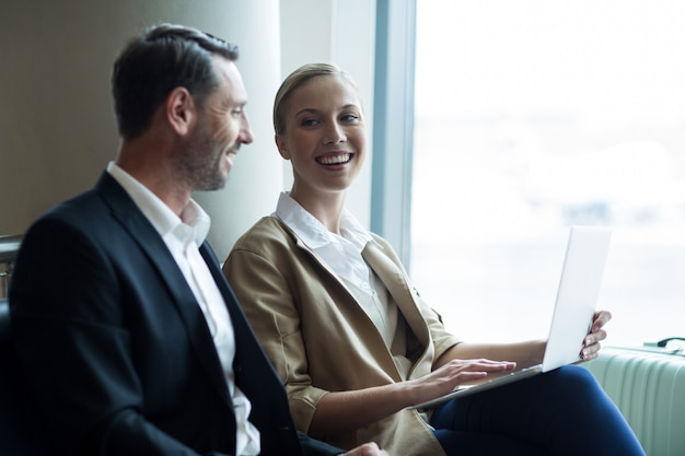 Businesspeople discussing over laptop