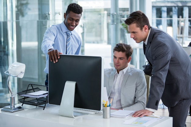 Businesspeople discussing at table over computer