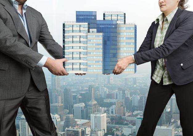 Бизнесмены борются, держа в руках большие офисные здания