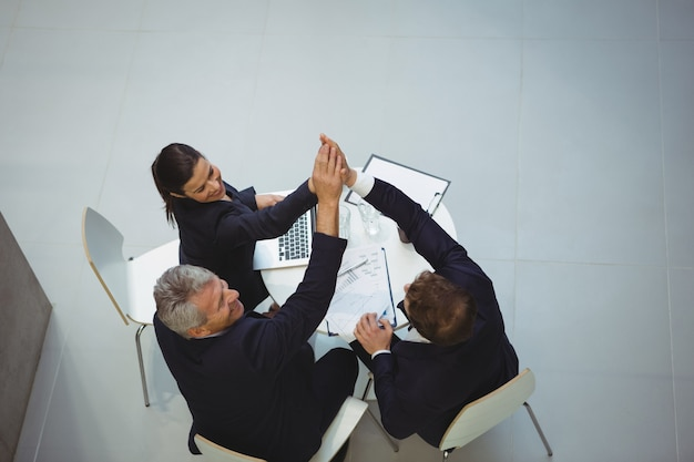 Businesspeople giving a high five to each other