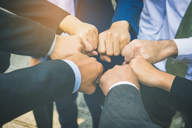 Businesspeople hands in fists in circle, business and teamwork concept