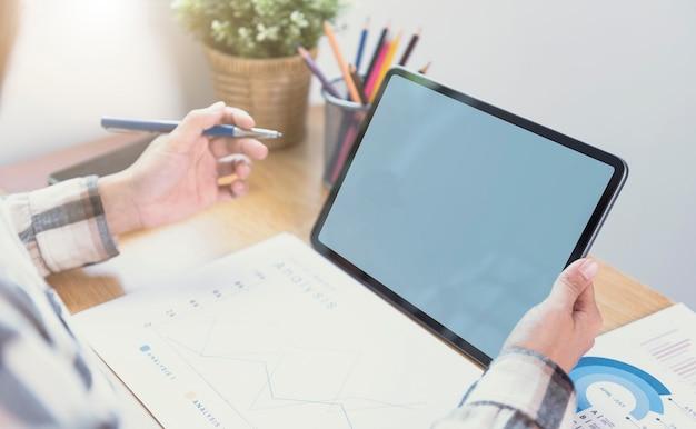 空白の画面でコンピューターのタブレットを使用してビジネスマンの手。タブレットコンピューターモニターのモックアップ。デザインやテキストの準備ができたスペースをコピーします。