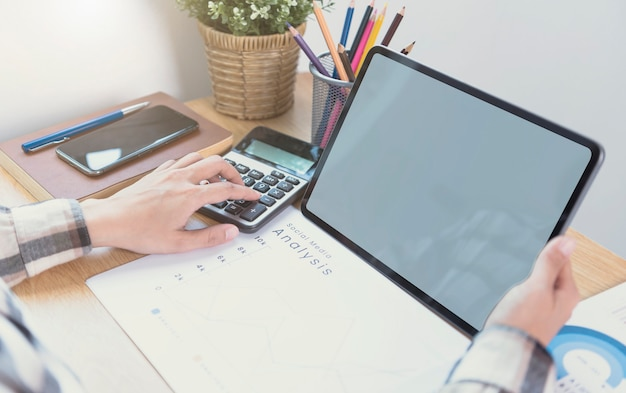 빈 화면이 있는 컴퓨터 태블릿을 사용하는 기업인 손. 태블릿 컴퓨터 모니터의 모형. 디자인 또는 텍스트를 위한 준비 공간을 복사합니다.