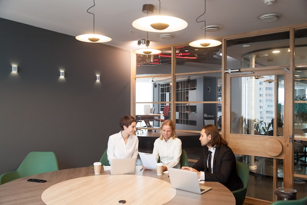 Businesspeople having discussion at team meeting in modern office interior