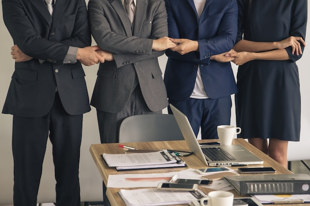 Businesspeople hold hands, stand in a row,  teamwork concept.