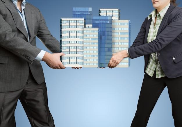 Бизнесмены, держащие в руках большие офисные здания