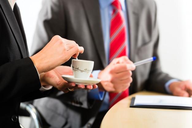 Бизнесмены в офисе пьют кофе