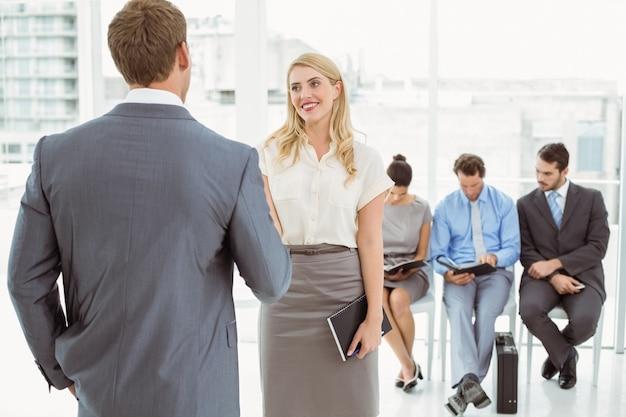 インタビューを待っている人の前にビジネスマン