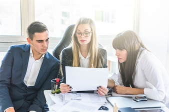 Businesspeople looking at document in office