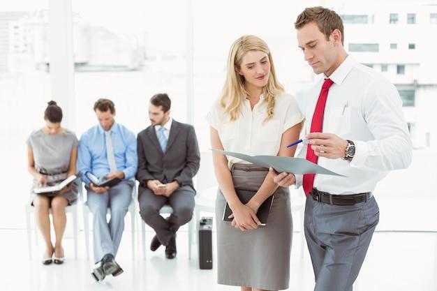 インタビューを待っている人に対してファイルを見ているビジネスマン