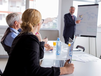Businesspeople looking at man giving presentation on flip chart
