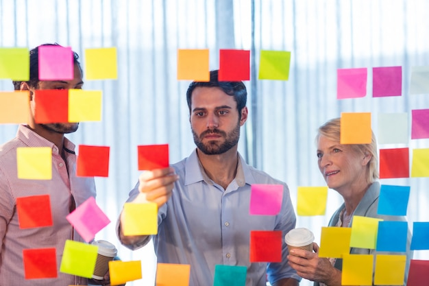 Businesspeople looking at sticky notes on the wall