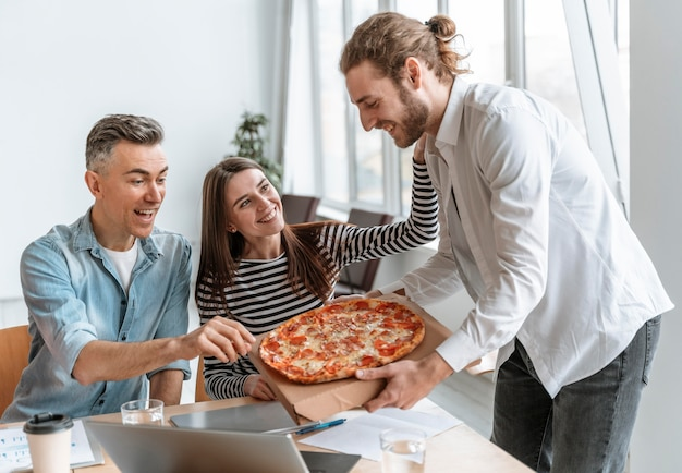 Businesspeople on lunch break eating pizza Premium Photo