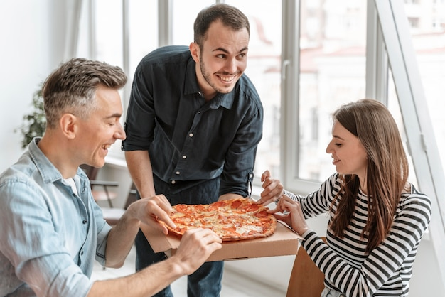 Businesspeople on lunch break eating pizza