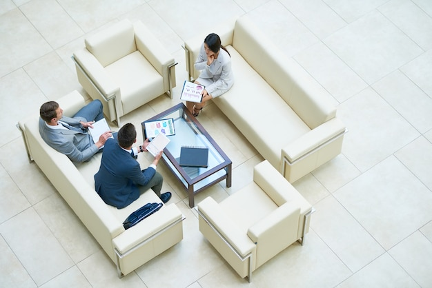 Businesspeople in a meeting on white sofas