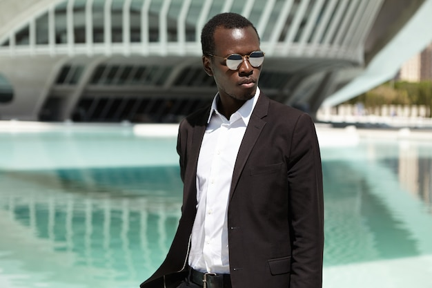 Businesspeople and modern urban lifestyle concept. attractive black european male entrepreneur walking to office after lunch at restaurant, posing in sunglasses and formal wear against seascape