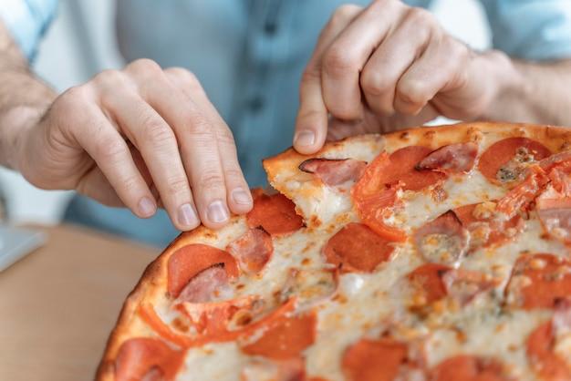 ピザを食べる昼休みのビジネスマンがクローズアップ