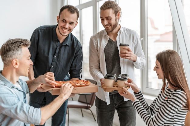 昼休みにピザを食べるビジネスマン