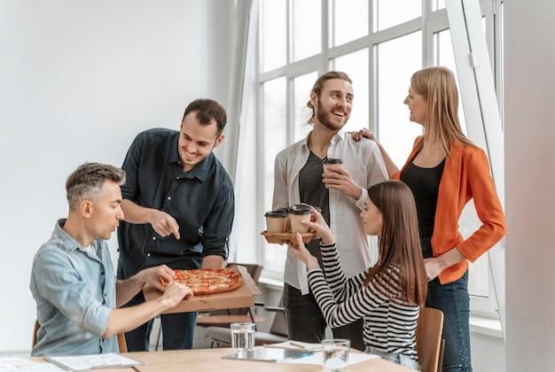 Бизнесмены на обеденном перерыве, едят пиццу