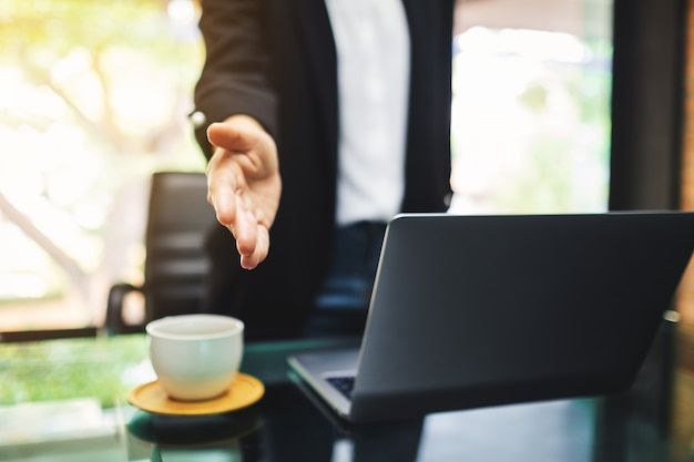 Бизнесмены открывают руки для рукопожатия с кем-то в офисе