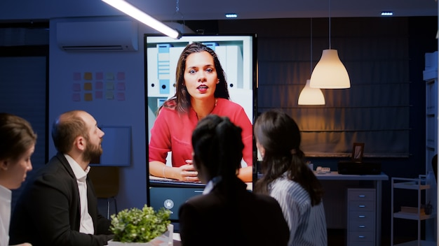 Businesspeople overworking in company office room having online videocall conference discussing marketing strategy late at night. remote businesswoman explaining deadline project in evening