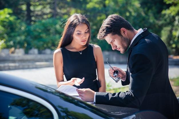 자동차 근처 야외에서 문서를 읽는 기업인