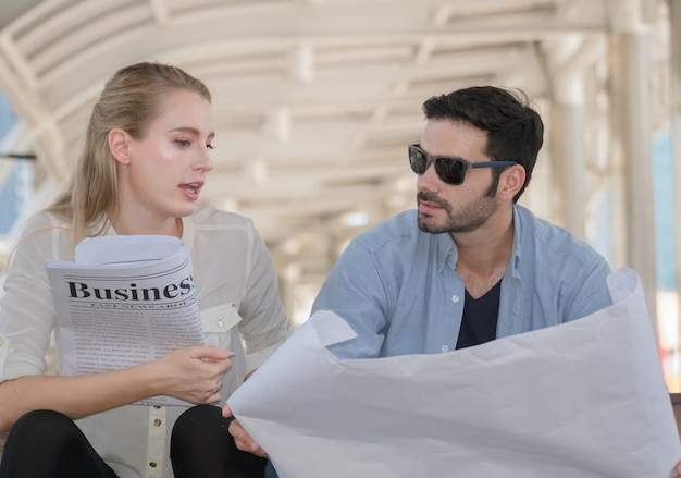 Businesspeople reading newspaper .happy couple reading newspaper concept.