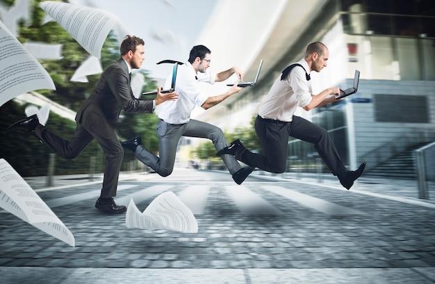 ビジネスマンは自分のラップトップで仕事に行くために通りを走ります