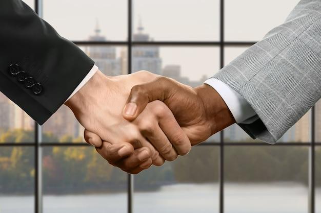 ビジネスマンは握手します。昼間のバックグラウンドでのビジネスハンドシェイク。私たちの交渉は成功しました。進歩の名において。