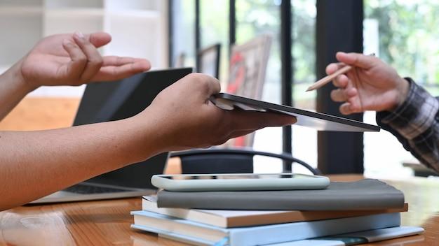 기업인들은 디지털 태블릿에서 정보를 공유하고 사무실에서 일에 대해 논의합니다.