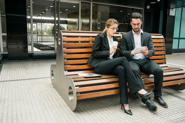 Businesspeople sitting on bench looking at mobile phone