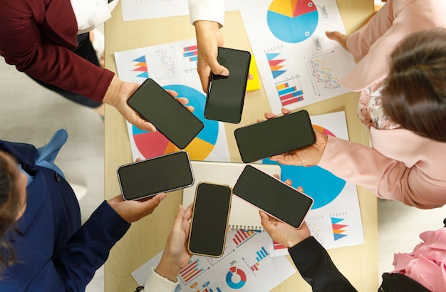 Businesspeople sitting together in office over working desk with colorful graph and charts pater, hold smartphones in different model with blank screens. taken from top view angle.