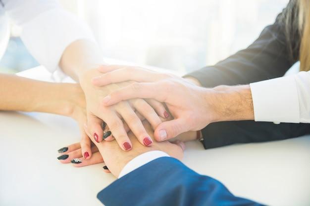 白い机の上にお互いの手を積み重ねるビジネスマン