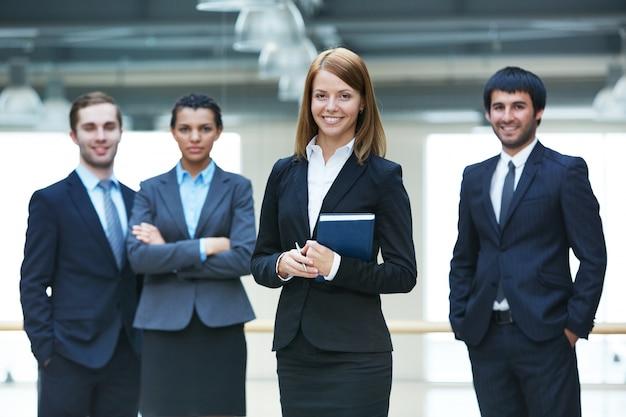 Бизнесмены, стоя вместе в офисе