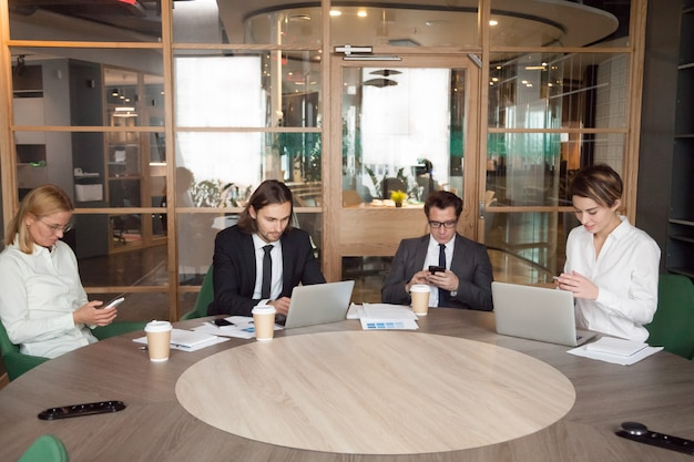 Businesspeople using devices during company business meeting