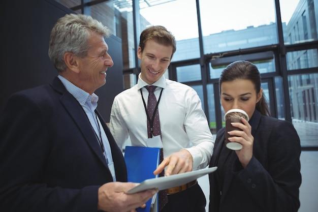 Бизнесмены с помощью цифрового планшета за чашкой кофе